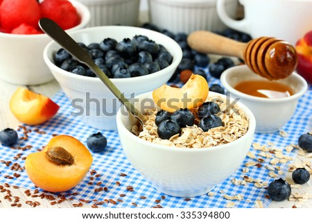 Healthy breakfast of muesli with honey, fresh blueberries and apricots - stock photo