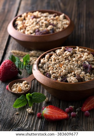 Healthy breakfast of muesli with strawberries, berries, milk and seeds on wooden background