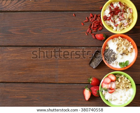 healthy breakfast of muesli, yoghurt, chia seeds, fruit and goji - stock photo
