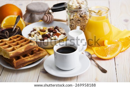 Healthy breakfast of oatmeal,coffee, wafers , apples, fresh juice, jam and oranges on a wooden background - stock photo