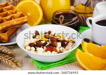 Healthy breakfast of oatmeal, fresh juice, jam and oranges on a wooden background