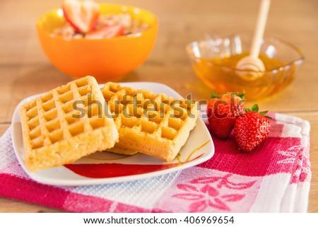 Healthy breakfast of waffles, strawberry, muesli and honey - stock photo