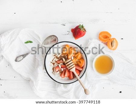 Healthy breakfast set. Rice cereal or porridge with fresh strawberry, apricots, almond and honey over white rustic wood backdrop, top view, copy space, horizontal - stock photo