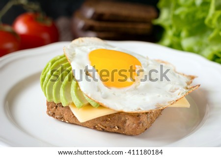 Healthy breakfast, sunny side up egg on whole grain toast with sliced avocado and cheese - stock photo
