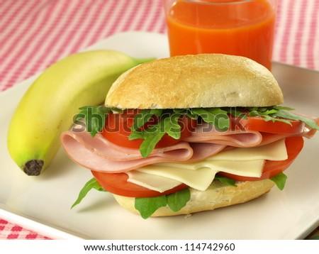Healthy breakfast with bun, juice and banana - stock photo