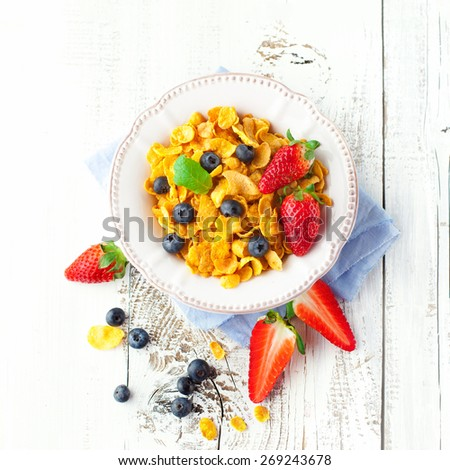 Healthy breakfast with cornflakes and fresh berries on white wooden background, top view - stock photo