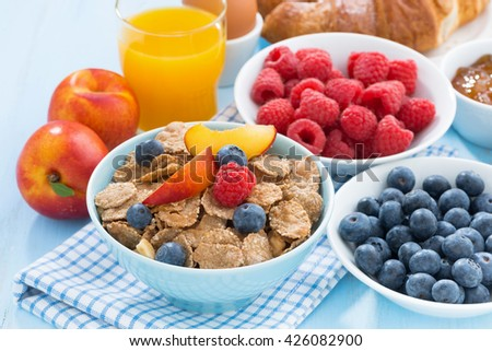 healthy breakfast with flakes, fresh fruit and berries on table, close-up - stock photo
