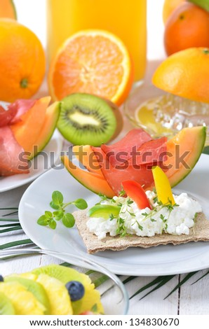 Healthy breakfast with fresh fruit, crispbread with cottage cheese and lean ham on melon