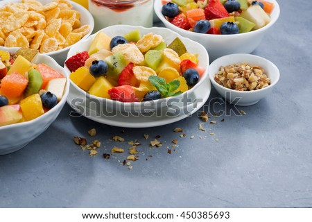 healthy breakfast with fresh fruit salad on grey background, horizontal