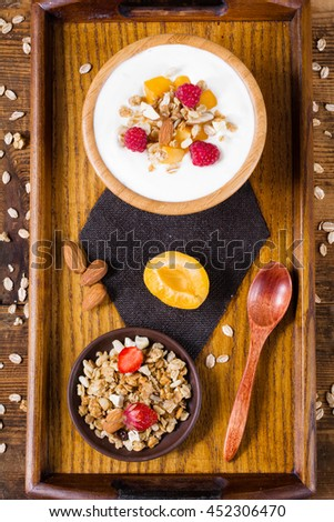 Healthy breakfast with fresh yogurt, homemade granola, almonds, apricots, peaches, strawberries and raspberries on a wooden serving tray with cute wooden spoon. Table top view. - stock photo