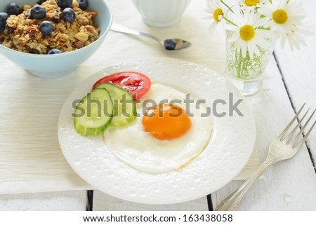 Healthy breakfast with fried egg and muesli - stock photo