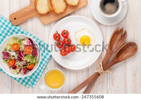 Healthy breakfast with fried egg, toasts and salad on white wooden table - stock photo