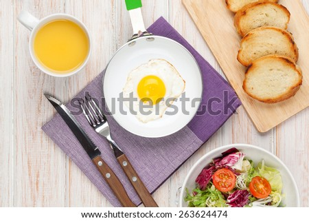 Healthy breakfast with fried egg, toasts and salad on white wooden table. Top view - stock photo