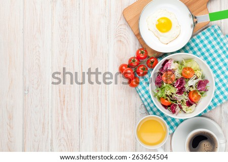 Healthy breakfast with fried egg, toasts and salad on white wooden table. Top view with copy space - stock photo