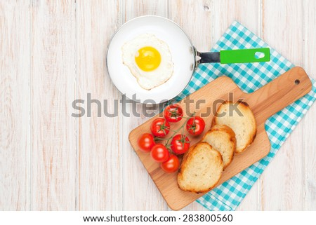 Healthy breakfast with fried egg, tomatoes and toasts on white wooden table. Top view with copy space - stock photo