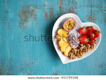 Healthy breakfast with fruits and chia seeds in heart shaped plate on blue background - stock photo