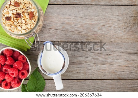 Healthy breakfast with muesli, berries and milk. View from above on wooden table with copy space - stock photo