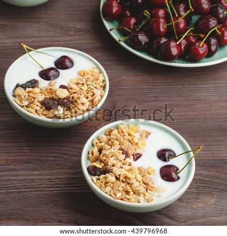 Healthy breakfast with muesli, yogurt and ripe cherries. - stock photo