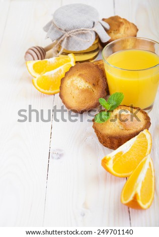 Healthy breakfast with muffins,juice,orange and honey on a wooden background - stock photo