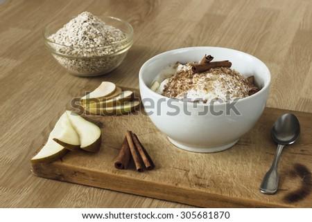 Healthy breakfast with oatmeal, pear, apple, coconut milk and cinnamon - stock photo