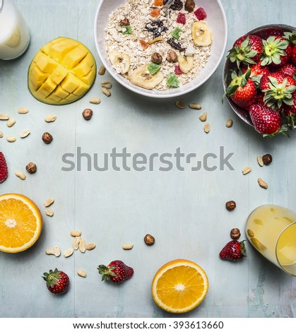 healthy breakfast with porridge, strawberries, fresh orange juice, mango and nuts place for text,frame on wooden rustic background top view - stock photo