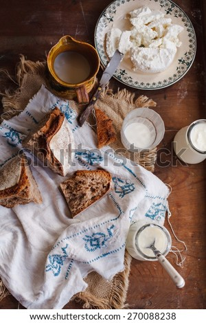 Healthy breakfast with whole bread, cottage cheese, yogurt and milk. Rustic scene with bread, milk, cheese and milk over napkin texture. Old food concept. Top view. - stock photo