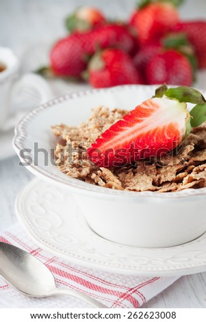 Healthy breakfast with wholegrain flakes, milk and fresh berries on white wooden table, selective focus