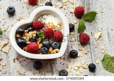 Healthy breakfast yogurt bowl / Yogurt with fresh berries granola and nuts in heart shaped bowl - stock photo
