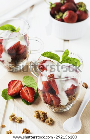 Healthy breakfast. Yogurt, granola and fresh strawberries in glass on a white wooden table background.Selective focus.  - stock photo