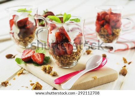 Healthy breakfast. Yogurt,granola and fresh strawberries in glass on white wooden table background.Selective focus. - stock photo