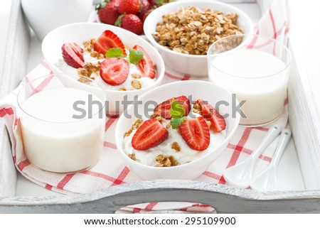 healthy breakfast - yogurt, strawberries, granola and milk on a tray, close-up - stock photo