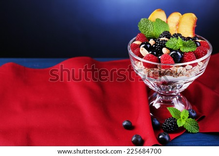 Healthy breakfast - yogurt with  fresh fruit, berries and muesli served in glass bowl on color wooden table, on dark color background - stock photo