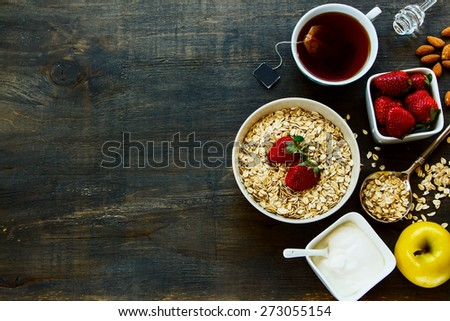 Healthy Breakfast. Yogurt with muesli, berries and tea over dark old wood. Health and diet concept. Top view. - stock photo