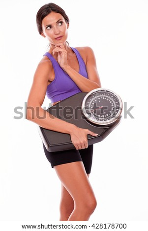 Healthy brunette woman with a scale, looking away thoughtfully, hand to chin while wearing her hair tied back and violet and black gymnastic clothing, isolated - stock photo