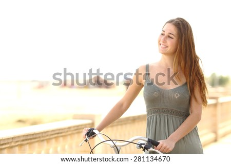 Healthy candid teen girl taking a walk with a bike on the beach in summer - stock photo