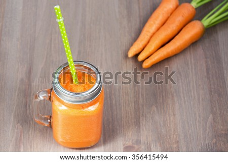 Healthy carrot smoothie in a jar with tube wooden background. Shallow dof - stock photo
