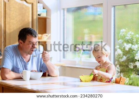Healthy caucasian family of two, young happy father and his little daughter, cute toddler girl, having breakfast together in sunny kitchen with big bright garden view windows. Selective focus on child - stock photo