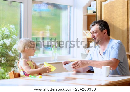 Healthy caucasian family of two, young happy father and his little daughter, cute toddler girl, having breakfast together in sunny kitchen with big bright garden view window. Selective focus on father - stock photo
