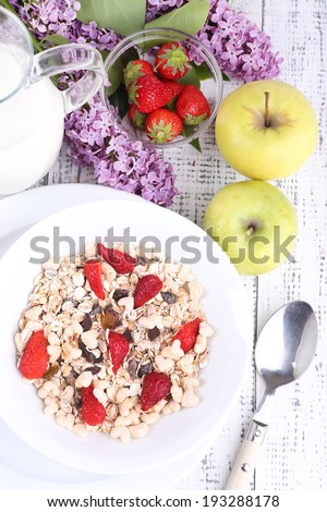 Healthy cereal with milk and fruits on wooden table - stock photo