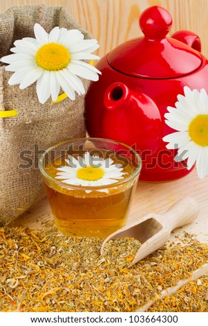 healthy chamomile tea, red teapot and sack with daisies