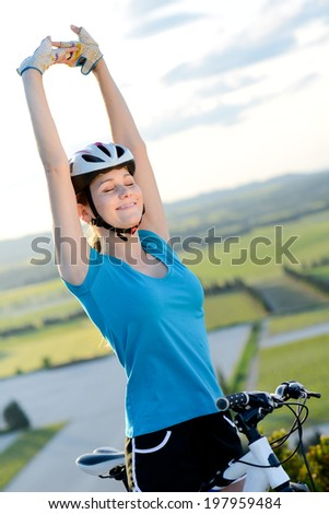 healthy cheerful young woman on mountain bicycle happy rising hands outdoor behind a beautiful countryside lanscape - stock photo