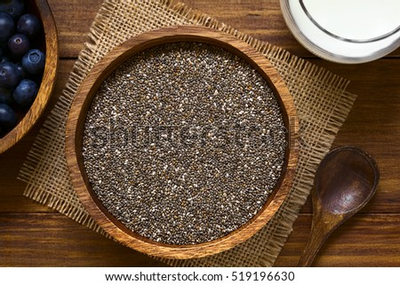 Healthy chia seeds (lat. Salvia hispanica) in wooden bowl with blueberries and milk on the side, photographed overhead with natural light (Selective Focus, Focus on the top of the chia seeds)