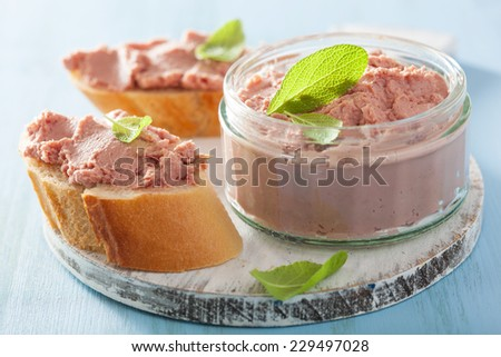 healthy chicken liver pate with sage in jar and on bread - stock photo