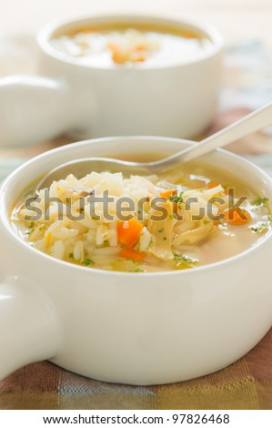Healthy chicken rice soup with spoon. Shallow depth of field. - stock photo
