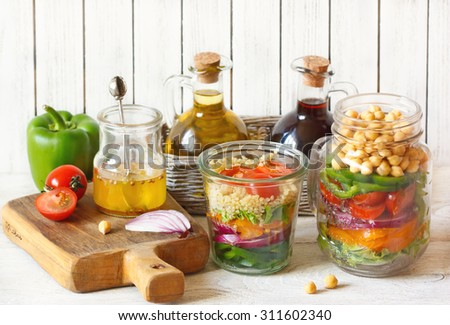 Healthy chickpeas and quinoa salads and fresh food ingredients on kitchen table. - stock photo