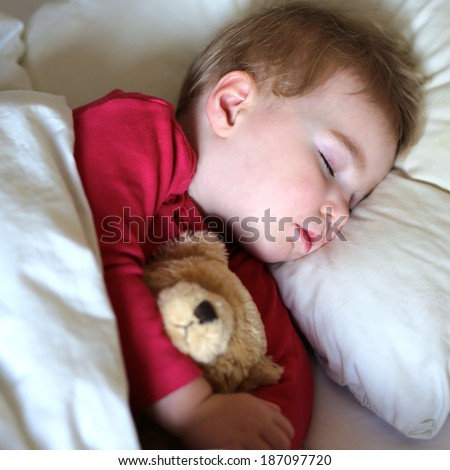 Healthy child, sweetest blonde toddler girl sleeping in bed holding her teddy bear