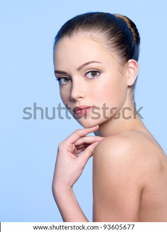 Healthy clean skin of young beautiful woman - blue background - stock photo
