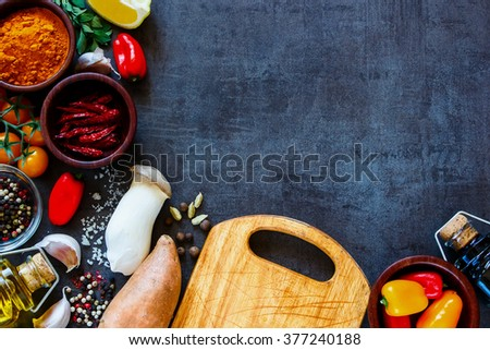 Healthy colorful farm vegetables and ingredients for tasty cooking on rustic background with space for text, border, top view. Vegetarian or diet food concept. - stock photo