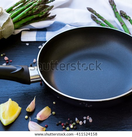 Healthy concept. Bunch of organic fresh asparagus with ingredients for cooking and frying pan on a grunge stone table. Selective focus, copy space background - stock photo