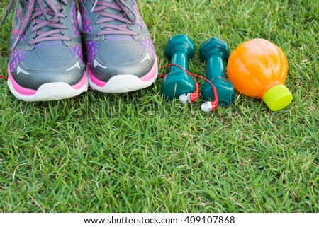 Healthy concept , diet plan with sport shoes and bottle of orange juice and Dumbells on green grass background